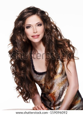 Beautiful adult woman with long brown curly hair. Fashion model over white background