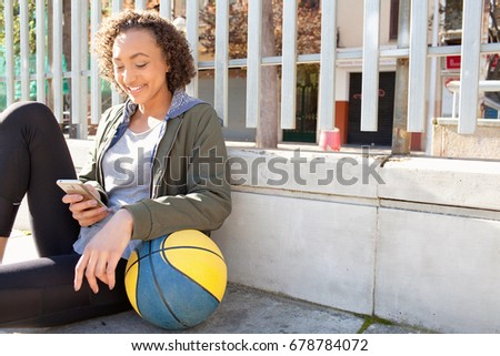 Beautiful african american adolescent girl in urban basket ball court with basketball using smart phone, networking smiling, outdoors. Black teenager technology, sport activities recreation lifestyle.
