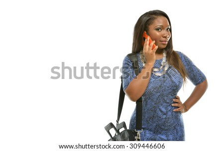 Beautiful African-American business  woman in blue dress and in studio - carrying briefcase and talking on phone - stock photo