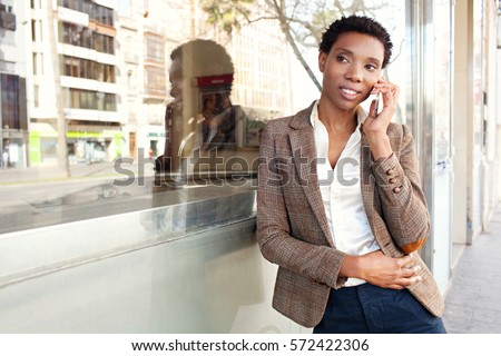 Beautiful african american business woman with office building glass with city reflections, smiling outdoors. Professional black woman in smart phone conversation call, lifestyle technology.
