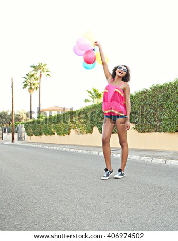 Beautiful african american teenager girl smiling at the camera in a home exterior suburban street, holding colorful balloons up in the air, outdoors. Fashionable fresh fun retro adolescent, lifestyle. - stock photo