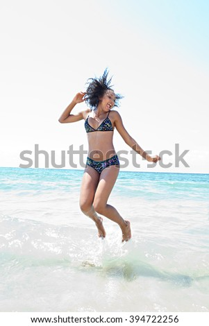 Beautiful african american teenager young woman bathing in the blue sea, joyfully jumping up on a sunny summer holiday, coastal exterior. Adolescent travel lifestyle enjoying the sun, body figure. - stock photo