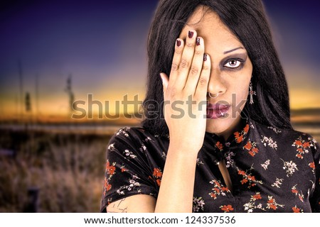 Beautiful african american woman covering her eye with one hand. Blurred beach sunset or sunrise blurred behind her. Missing the beauty around her. - stock photo