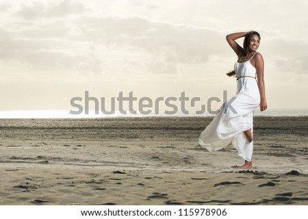 Beautiful African American woman doing dance pose with a smile at the beach. - stock photo
