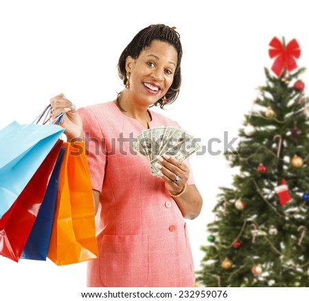 Beautiful African-american woman holding shopping bags and money.  Isolated on white, in front of a Christmas tree.   - stock photo