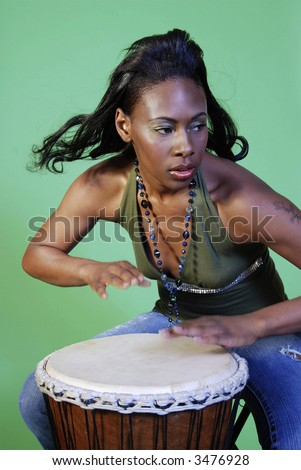 Beautiful African-American woman playing a drum. - stock photo