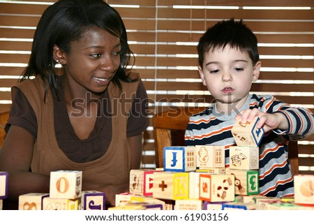 Beautiful african american woman playing alphabet blocks with a 3 year old boy in kitchen.