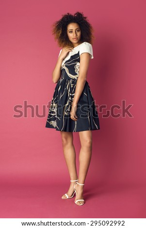 Beautiful African American woman posing in nice dress on a pink background. Fashion photo with afro hairstyle.
