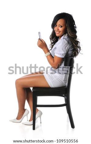 Beautiful African American woman seated on black chair using cellphone