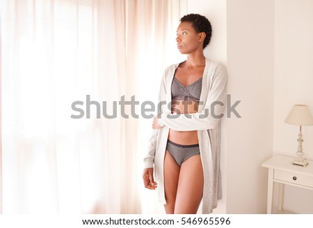 Beautiful african american woman wearing robe and lingerie in bedroom with light filtering through curtains, home interior. Health and intimacy, beauty lifestyle, moody indoors. Body silhouette.
