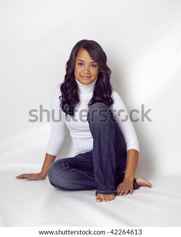 beautiful african american woman wearing white turtleneck and blue jeans sitting on white background in bare feet - stock photo