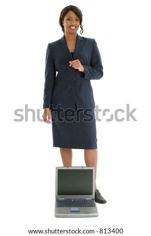 Beautiful African American 24 year old business woman in suit standing  behind an open laptop.