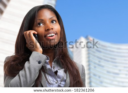 Beautiful african businesswoman on the phone outdoor - stock photo