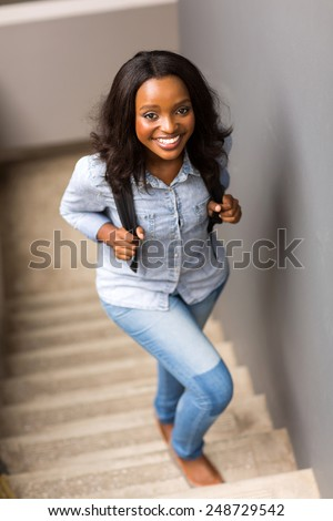 beautiful african college girl walking up the stairs on campus - stock photo