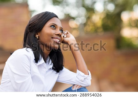 beautiful african college student daydreaming on campus - stock photo
