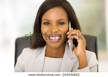 beautiful african corporate worker talking on mobile phone in office