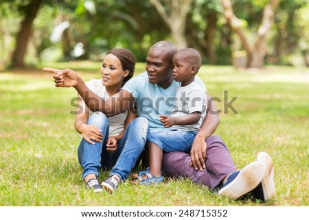 beautiful african family sitting on grass in the park - stock photo