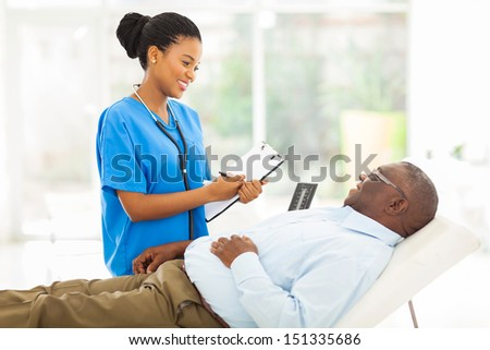 beautiful african female doctor consulting senior patient in office - stock photo