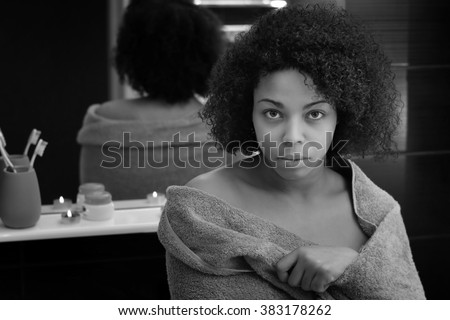 Beautiful african girl in the bathroom near the mirror - stock photo