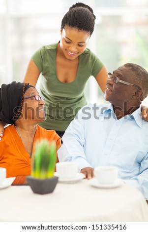 beautiful african girl talking to senior parents at home - stock photo