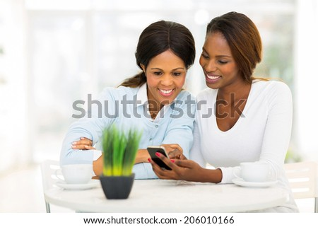 beautiful african mother and daughter using smart phone at home - stock photo