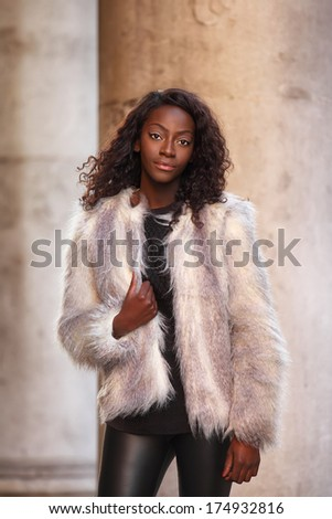 beautiful african woman dressed in fur coat posing outdoors - stock photo