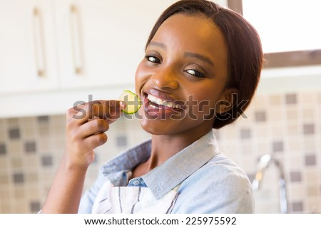 beautiful african woman eating a slice of cucumber in kitchen - stock photo