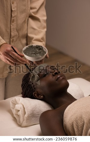 Beautiful african woman having clay facial mask applying by beautician - stock photo
