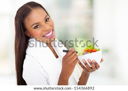 beautiful african woman holding bowl of green salad - stock photo