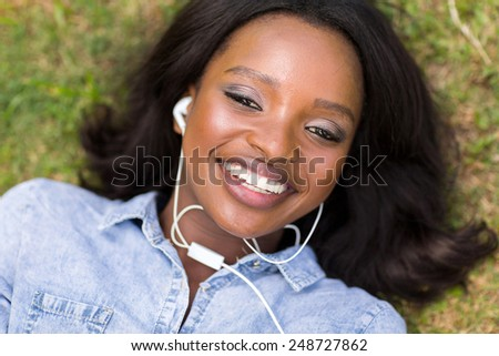 beautiful african woman listening to music outdoors - stock photo
