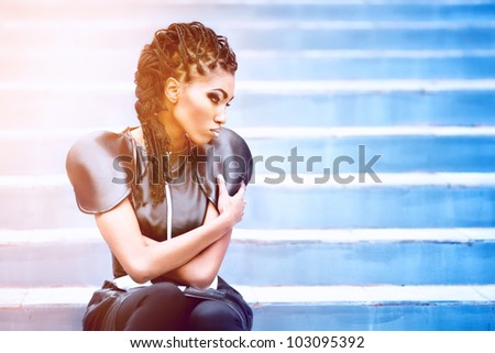 Beautiful african woman sitting whith fashion make-up - stock photo