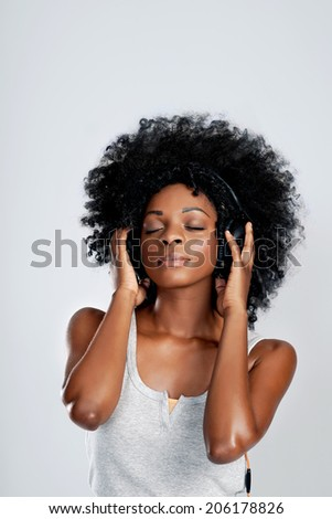 Beautiful african woman with afro listening to music with eyes closed in studio - stock photo