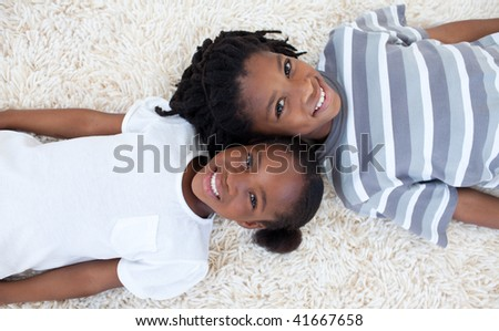 Beautiful Afro-American brother and sister on floor with heads together - stock photo