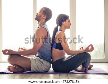 Beautiful Afro American couple in sports clothes is meditating sitting back to back in lotus position on mat while doing yoga at home