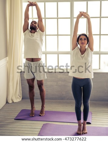 Beautiful Afro American couple is smiling while doing yoga, standing on mat at home