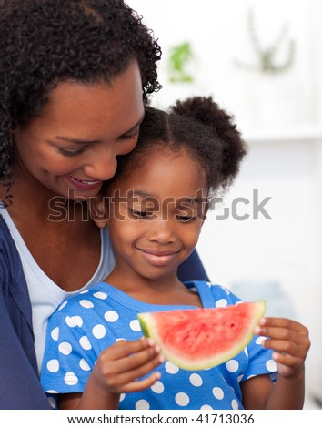 Beautiful Afro-american girl eating watermelon with her mother - stock photo