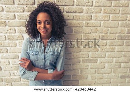 Beautiful Afro American girl is looking at camera and smiling while standing with crossed arms against white brick wall - stock photo