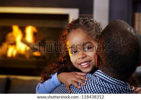 Beautiful afro little girl hugging father at home by fireplace, smiling. - stock photo