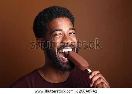 Beautiful afro man with ice-cream in front of a brown background
