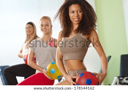 Beautiful afro woman exercising with ball at the gym, smiling. - stock photo