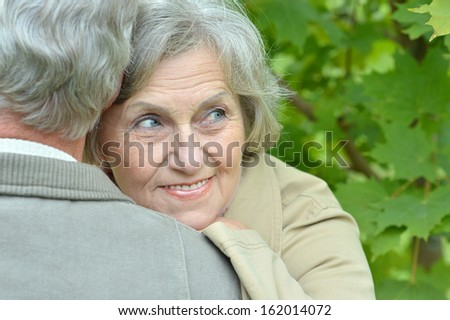 beautiful aged couple walking in the park in September