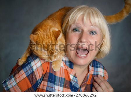Beautiful aged woman hugging her red cat on grey background. - stock photo