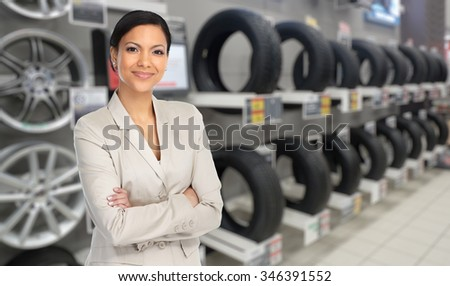 Beautiful agent woman in car repair service over tire background. - stock photo