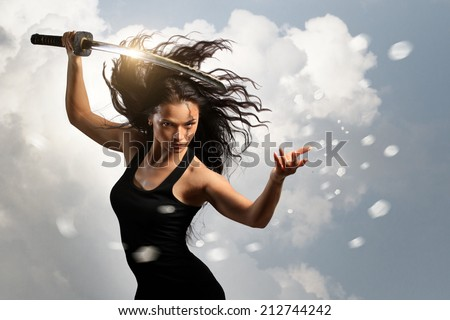 Beautiful aggressive Brunette holding katana sword with cloudy environment - stock photo