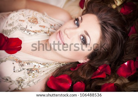 Beautiful alluring woman lying on bed in roses with glossy hair.Young happy lady in luxury bedroom smiling and waiting for her lover. Sexy girl in lingerie relaxing in red petals. Erotic concept