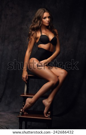 Beautiful alluring young woman in sexy lingerie sitting on a chair - stock photo