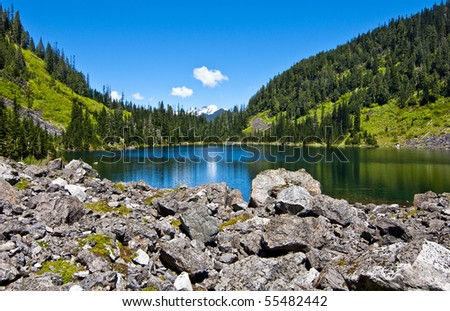 Beautiful alpine lake on a sunny day. Lake 22 is nestled in between snow covered mountains and grassy hills in western Washington. - stock photo
