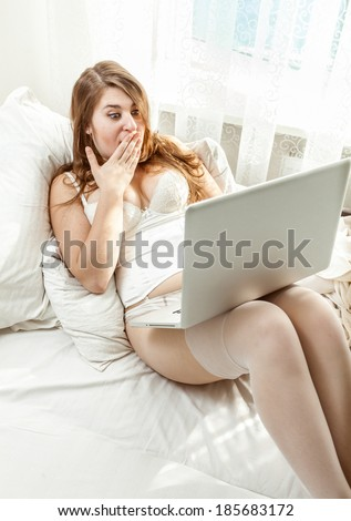 Beautiful amazed woman having video conference while lying in bed - stock photo