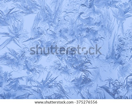 beautiful amazing unusual ice patterns on window glass in winter and freezing cold blue shadows - stock photo