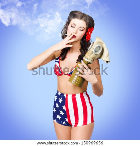 Beautiful American army pin-up girl smoking cigarette while holding military issued gas mask on blue background - stock photo